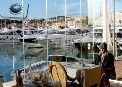 Fermeture d'une terrasse d'un café restaurant à Mèze entre Sète et Agde, Hérault. Les rideaux de verres permettent une utilisation de l'espace extérieur toute l'année.
